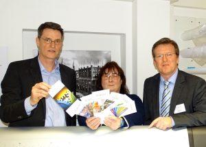 Zeigen bei der Eröffnungsfeier Produkte aus der Druckerei: ADiNet-Leiter Tilman Schomerus, Druckerei-Beschäftigte Claudia Kuhlen und BRÜCKE-Geschäftsführer Frank Nüsse (v.l.)