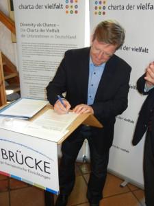 """9. Juni 2015: Frank Nüsse unterschreibt die """"Charta der Vielfalt"""" für die BRÜCKE"""
