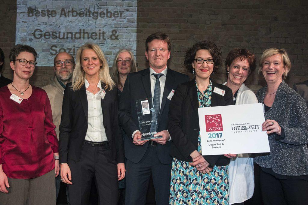 BRÜCKE-Beschäftigte bei der Preisvergabe, in der Mitte Geschäftsführer Frank Nüsse.