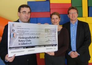 Dr. Ole Krönert (links) von den Rotary Clubs Lübeck bei der Spendenübergabe an BRÜCKE-Geschäftsführer Frank Nüsse und Einrichtungsleiterin Diana Kuchenbecker